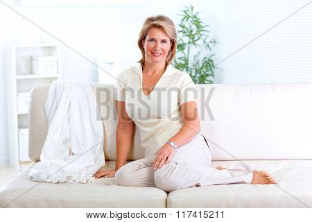 Senior woman relaxing in modern apartment.