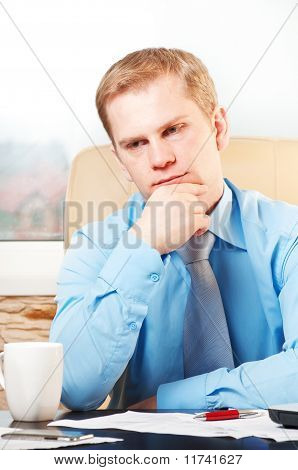 portrait of a young thoughtful businessman in doubt about something