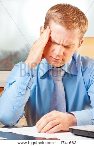 Portrait of a young businessman with headache