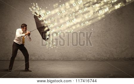 Business man holding umbrella against dollar rain concept on grungy background