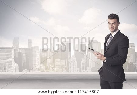 A young adult businessman standing in front of city landscape with skyscraper buildings and clouds concept