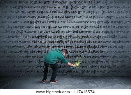 Young urban painter drawing random letters on the wall