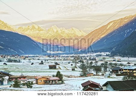 View On Countryside In Snow Covered Switzerland At Sunset