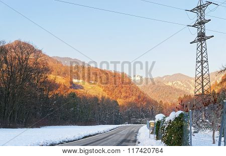 View Of Road With Electricity Transmission Line In Switzerland In Winter
