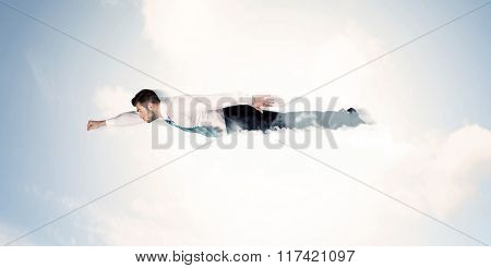 Business man flying like a superhero in clouds on the sky concept