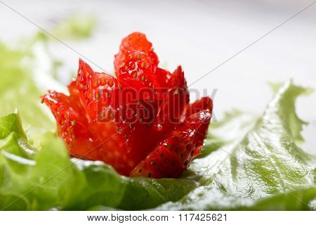 Red Flower From Strawberry On A Green Lettuce Leaf