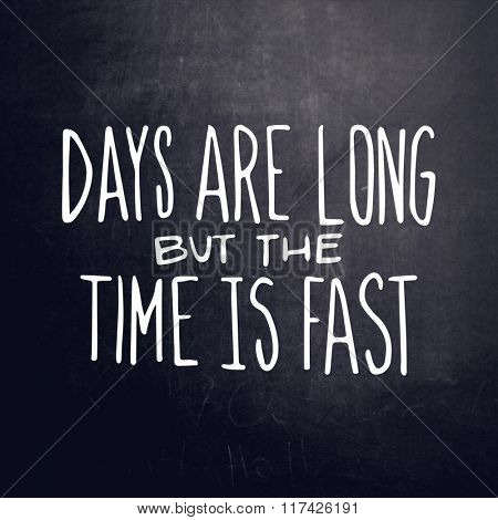 Inspirational Typographic Quote on black chalk board  - Days are long but the time is fast