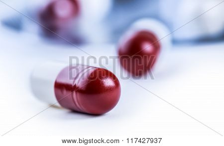 Pills. Tablets. Capsule. Heap of pills. Medical background. Close-up of pile of red white tablets