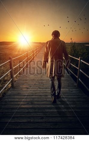 A man with long coat walking in a boardwalk into de sunset