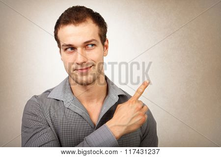 Happy young isolated man pointing finger