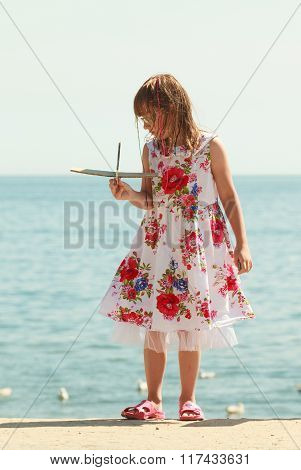 Little Girl Kid At Beach With Paper Plane Airplane