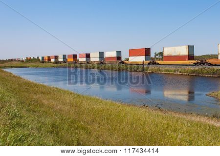 Reflections Of Container Train In Pond