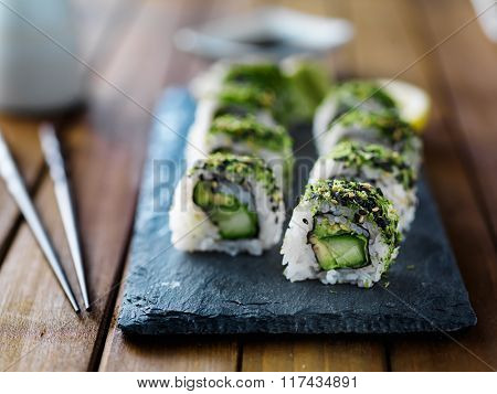healthy kale, avocado and cucumber sushi roll on slate serving tray