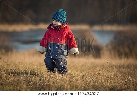 Young Happy Boy Playing Outdoor In Spring Landscape Near Lake