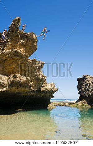 People jumping off a cliff into rock pool