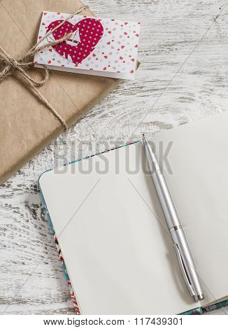 Valentine's Day Gifts In Kraft Paper, Homemade Valentine's Day Card And A Clean Open Notebook On A W
