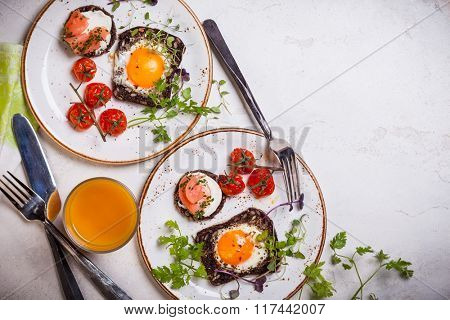 Fried eggs on slices of whole grain bread, salmon canape and baked cherry tomatoes