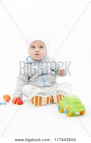 caucasian baby boy playing with cars warm clothing hat studio shot isolated on white