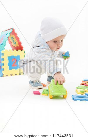little child baby playing with toys isolated on white studio shot