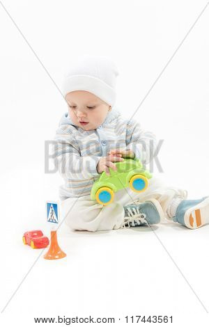 caucasian baby boy child 1 year playing with cars sitting on the floor isolated on white studio shot