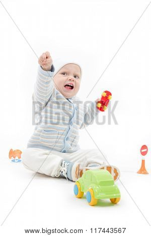 caucasian baby boy child 1 year sitting on the floor playing with cars crying warm clothing hat isolated on white studio shot