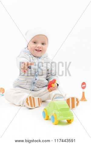 little child baby smiling playing with cars isolated on white studio shot warm clothing hat