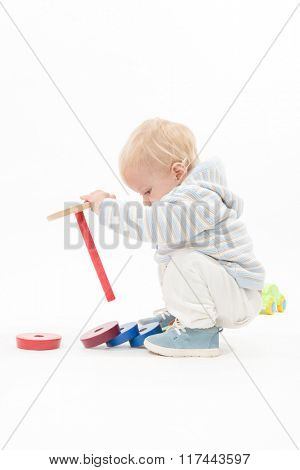 little child baby boy playing pyramid wooden toy blue isolated on white studio shot