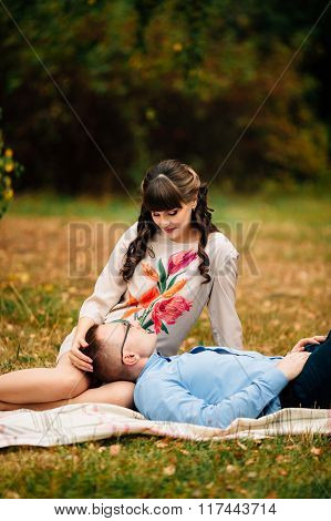Handsome Husband Lying On His Young Pregnant Beautiful Woman's Leg In Park.