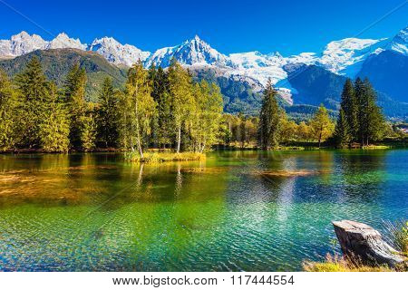 City Park is illuminated by sunset. The lake reflected the snow-capped Alps and evergreen spruce. The mountain resort of Chamonix, Haute-Savoie