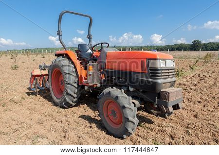 Small Red Tractor With Plow In Field.