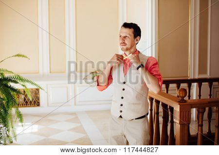 Stylish And Handsome Groom Tying His Tie In Morning Of The Wedding Day.
