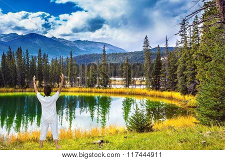 Woman, dressed for yoga, Sun Salutation on the bank of round lake. Jasper National Park in the Rocky Mountains. Patricia Lake