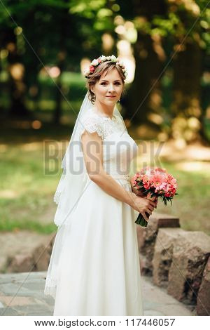 Beauty Bride In Bridal Gown With Bouquet On The Nature.