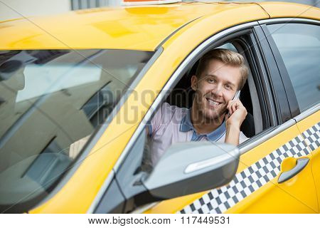 Driver talking on the phone in a yellow taxi