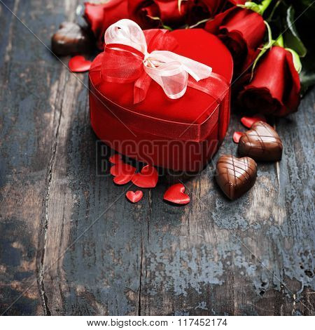 Valentine composition with roses and gift box on wooden background