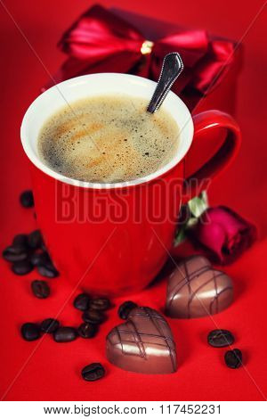 Valentine's day composition with coffee cup and chocolate on red background