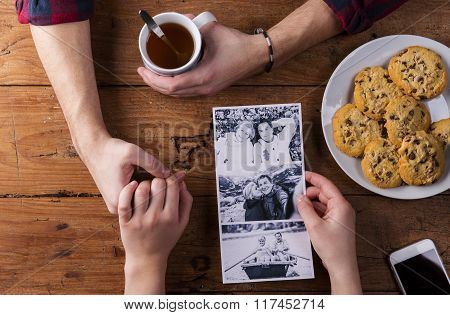 Mans and womans hands. Black-and-white photo. Couple. Tea and cookies.