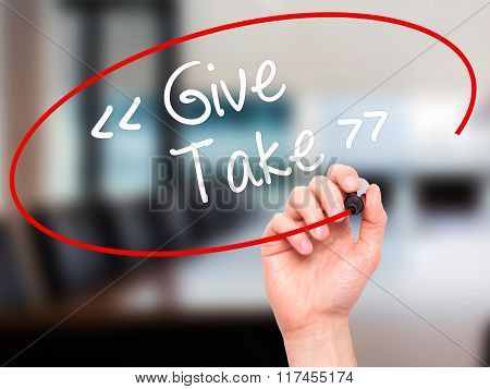 Man Hand Writing Give - Take With Black Marker On Visual Screen.