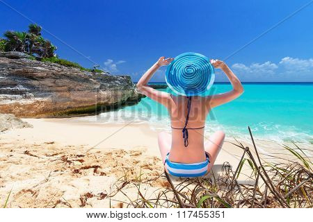 Woman in hat enjoying sun holidays on the tropical beach