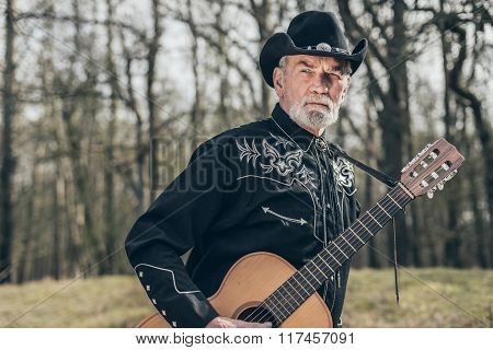 Bearded Elderly Musician With Guitar At The Forest