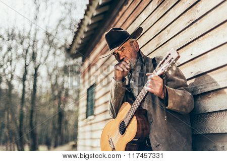 Senior Country-western Guitarist Leaning On A Wall
