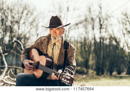 Elderly Musician Sitting Strumming A Guitar