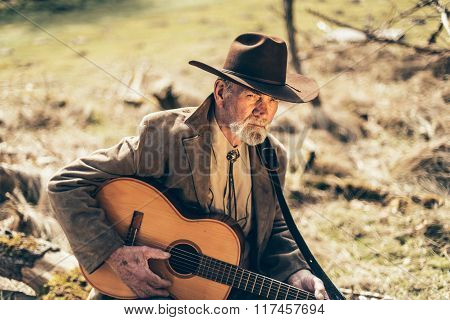 Lonely Senior Man Sitting Strumming His Guitar