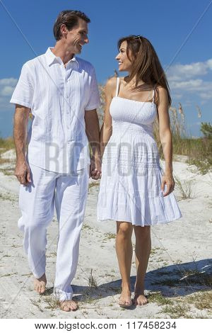 Middle aged man and woman romantic couple in white clothes walking on a deserted tropical beach with bright clear blue sky