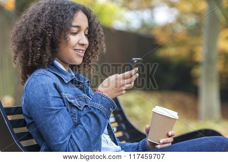 Beautiful happy mixed race African American girl teenager female young woman smiling drinking takeaway coffee and cell phone texting sitting on a park bench in autumn or fall