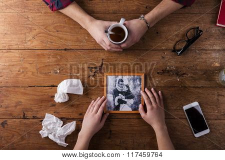 Sad mans, womans hands holding broken picture of romantic couple.