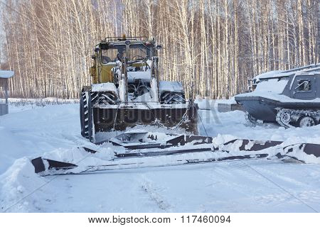 Big russian wheeled tractor with wedge. Forest snow sunny day Russia Siberia