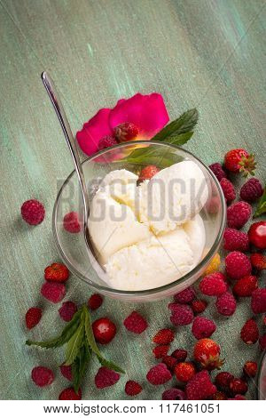 Ice Cream In Transparent Glass Plates Scattered Around The Raspberries, Strawberries On A Turquoise