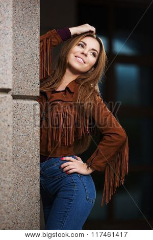Happy young fashion woman in leather jacket on city street
