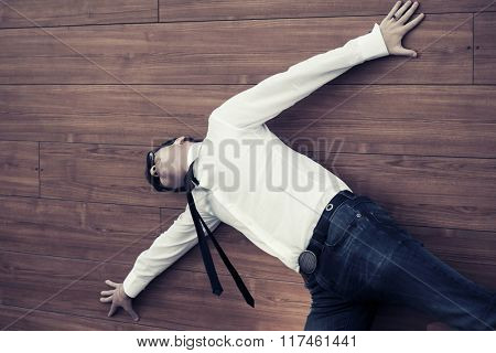 Young businessman in despair lying on the floor